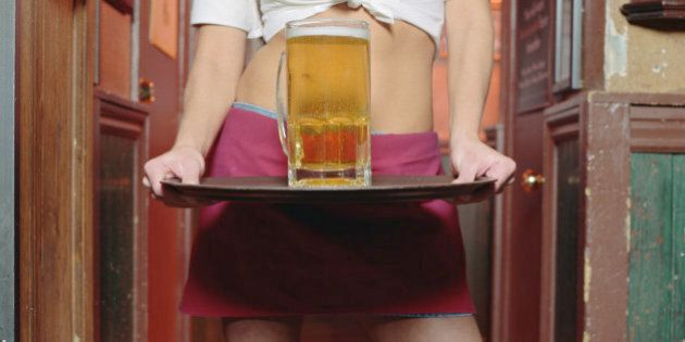 Young waitress holding glass of beer on tray, mid