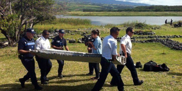 Police carry a piece of debris from an unidentified aircraft found in the coastal area of Saint-Andre...