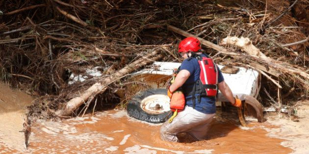 COLORADO CITY, AZ - SEPTEMBER 15: A search and rescue member searrches a buried vehicle in Short Creek...