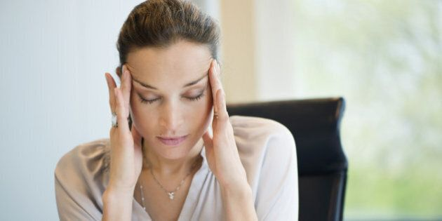 Close-up of a businesswoman suffering from a headache in an