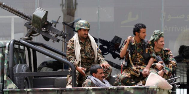 Shiite rebels, known as Houthis, wearing an army uniform, ride on an armed truck to patrol the international...