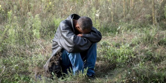 A refugee rests on a field at the Serbian-Hungarian border near Horgos, Serbia,Tuesday, Sept. 15, 2015....