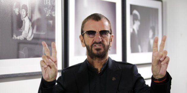 British musician Ringo Starr of legendary band The Beatles poses in front of an exhibition of photographs...