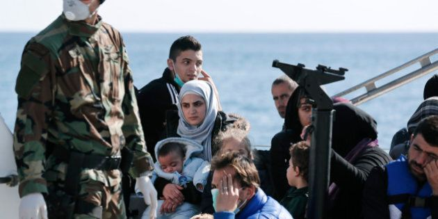 A Greek coast guard officer, wearing a mask for fear of infectious disease, stands next to a small group...