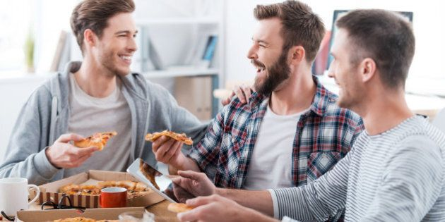Three happy young men eating pizza together while sitting in the