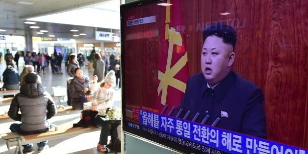 Travellers sit by a television screen showing North Korean leader Kim Jong-Un's New Year speech, at a...