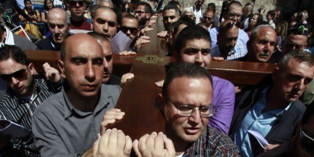 Catholic Arab worshippers of the local parish carry a wooden cross along the Via Dolorosa (Way of Suffering)...