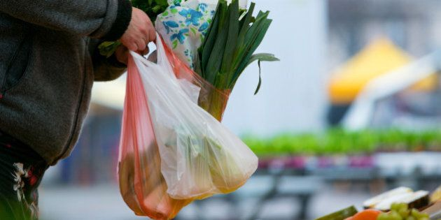 A customer holds vegetables in plastic carrier bags at an open air market in Berlin, Germany, on Wednesday,...