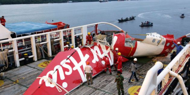 Crew members of Crest Onyx ship prepare to unload parts of AirAsia Flight 8501 from a ship at Kumai port...