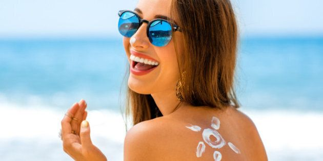 Young woman with sun shape on the shoulder holding sun cream bottle on the