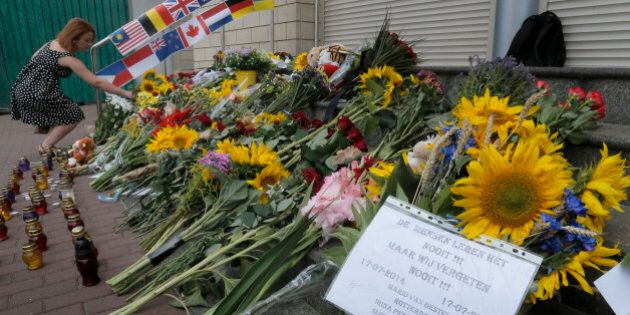 People lay flowers at the Netherlands Embassy for the Malaysia Airlines Flight MH17 crash victims, in Kiev, Ukraine, Friday, July 17, 2015. Residents of the Ukrainian village where the Malaysian airliner was shot down with 298 people aboard a year ago joined a procession to the crash site on Friday, while Australia's prime minister remembered the