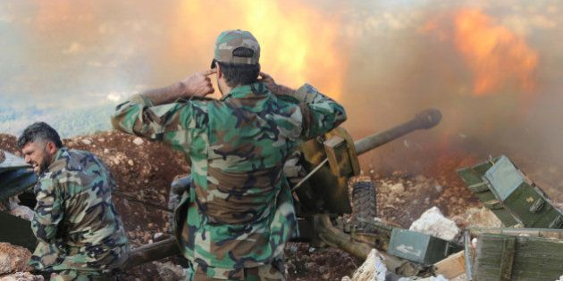 In this photo taken on Saturday, Oct. 10, 2015, Syrian army personnel fire a cannon in Latakia province,...