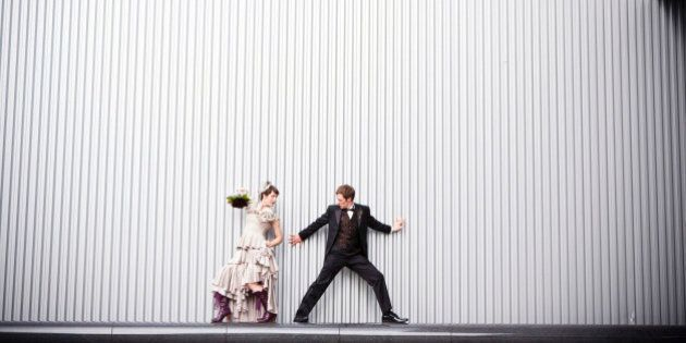 Playful bride and groom standing near
