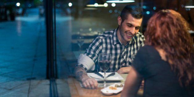 Young couple in modern restaurant having dinner