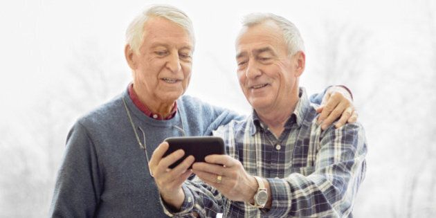 Senior gay couple shooting a selfie / sharing images / video conferencing with mobile phone in front...
