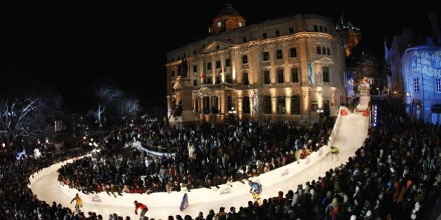 Racers make their way down the ice skating track at the Red Bull Crashed Ice competition Saturday, Jan....