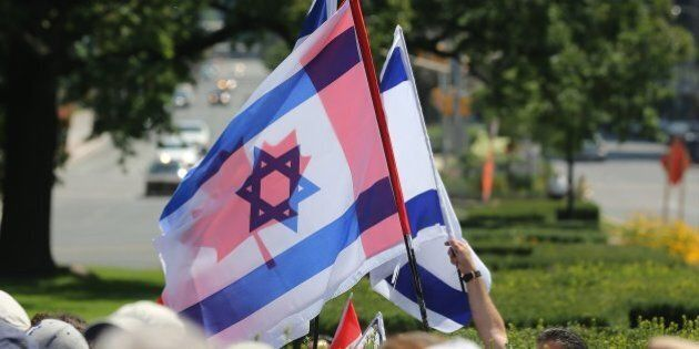 TORONTO, ON- JULY 27 - The Candian and Israeli flags fly together as Pro-Israel Torontonians gathered...