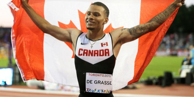 Canada's Andre De Grasse celebrates with a Canadian flag after winning the gold medal in the men's 100...