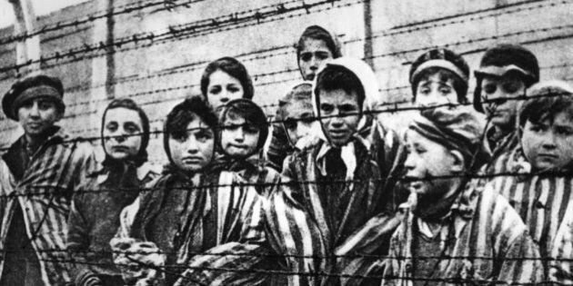 Children behind a barbed wire fence at the Nazi concentration camp at Auschwitz in southern Poland. (Photo...
