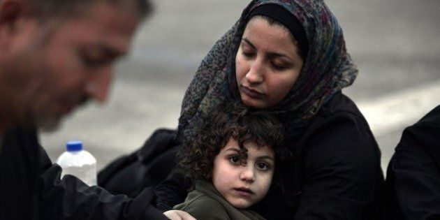 A Syrian mother tries to warm up her daugter after they arrived on the island of Lesbos, early on June...