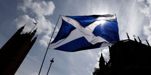 The Scottish flag flies above Parliament in Westminster, London, Monday, May 11, 2015. The separatist...