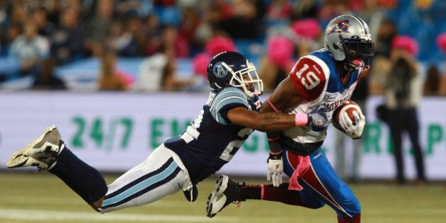TORONTO, ON - OCTOBER 18: Evan McCollough #24 of the Toronto Argonauts makes a tackle on S.J. Green #19...