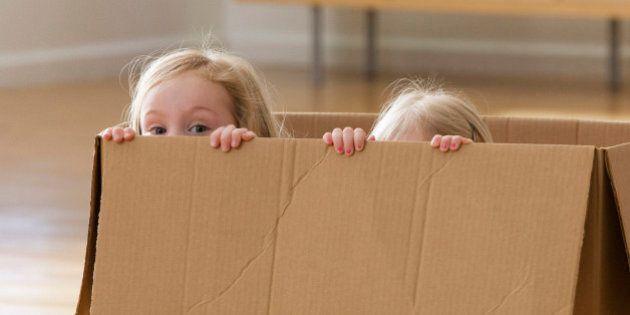 Caucasian sisters playing in cardboard