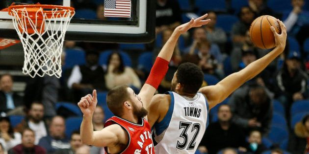 Minnesota Timberwolves center Karl-Anthony Towns (32) stretches out to shoot the ball against Toronto Raptors center Jonas Valanciunas (17) in the second half of an NBA basketball game Wednesday, Feb. 10, 2016, in Minneapolis. The Wolves won 117-112. (AP Photo/Stacy Bengs)