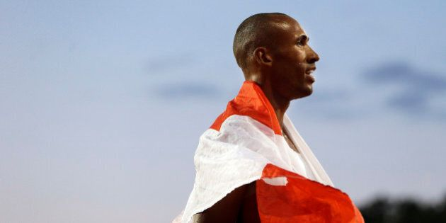 Decathlon champion Damian Warner of Canada wears a national flag following his win in the men's decathlon...