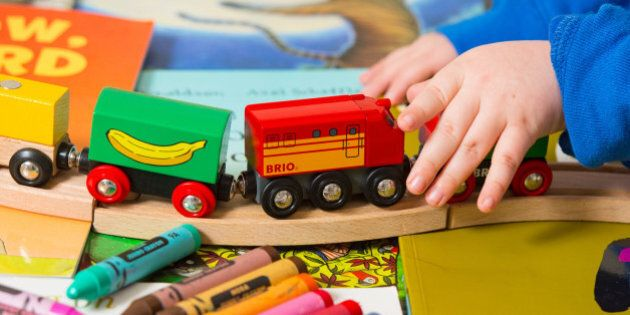 Generic stock photo shows a toddler playing with a selection of children's toys, including a train set...