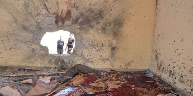 People look at blood stains from a damaged mosque following an explosion in Maiduguri, Nigeria, Friday,...