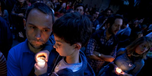 FILE- In this Monday, Nov. 16, 2015, file photo, a man holds a child in his arms outside of the French...