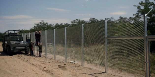 Hungarian soldiers build a fence near Morahalom, Hungary, Thursday, July 16, 2015. A fence on Hungary's...