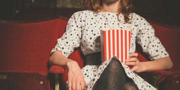 A young woman is sitting in a movie theater with a bucket of popcorn