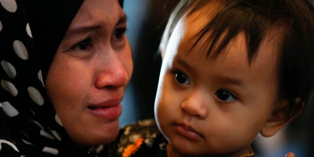 A family member of a Malaysia Airlines flight MH17 victim cries during a memorial service to mark the...