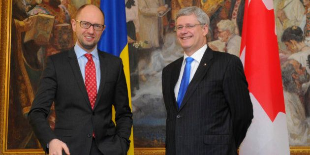 Ukrainian Prime Minister Arseniy Yatsenyuk, right, speaks with Canadian  Prime Minister Stephen Harper in Kiev, Ukraine, Saturday, March 22, 2014.  World leaders are gathering in Europe for a Nuclear Security Summit March 24-25, with the main topic of discussion expected to be the situation in Ukraine. (AP Photo/Andrew Kravchenko, Pool)