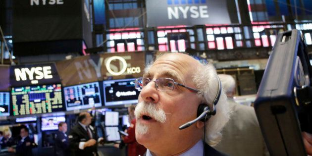 Stock trader Peter Tuchman monitors stock prices at the New York Stock Exchange, Monday, July 13, 2015.  U.S. stocks are opening higher after Greece reached an agreement with its creditors on a new loan package that will help keep the country in the euro. (AP Photo/Mark Lennihan)