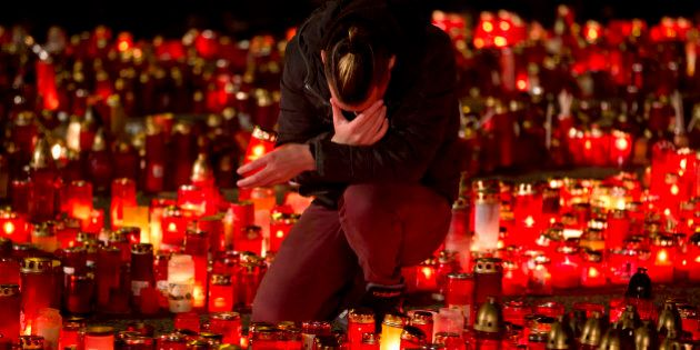 A man touches his forehead holding a candle outside the Colectiv nightclub in Bucharest, Romania, Friday,...