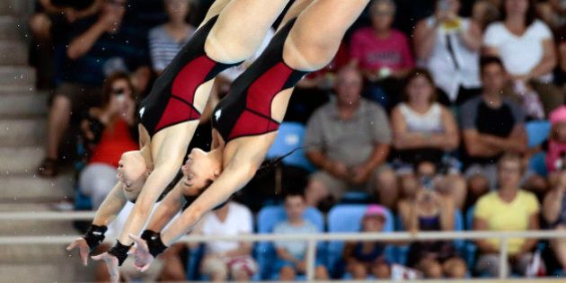 Meaghan Benfeito and Roseline Filion of Canada compete during the women's synchronized 10-meter platform diving event at the Pan Am Games Monday, July 13, 2015, in Toronto. The pair won the gold medal in the event. (AP Photo/Mark Humphrey)