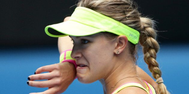 Eugenie Bouchard of Canada wipes the sweat from the face as she plays Maria Sharapova of Russia during their quarterfinal match at the Australian Open tennis championship in Melbourne, Australia, Tuesday, Jan. 27, 2015. (AP Photo/Rob Griffith)