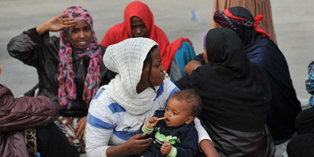 Migrants wait on the harbor after disembarking from British Royal Navy ship HMS Bulwark at Catania's...