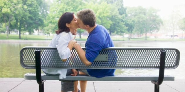 Parents kissing on bench in park