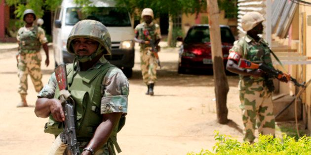 FILE - In this Thursday, June 6, 2013 file photo Nigerian soldiers stand guard at the offices of the...