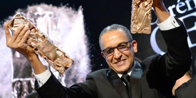 Mauritanian director Abderrahmane Sissako raises his trophies on stage after winning the Best Feature...