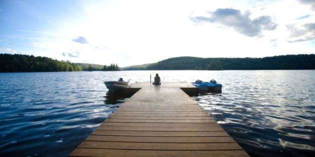 Person sitting on dock with two boats in