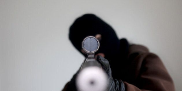 Man wearing a balaclava holding a sniper