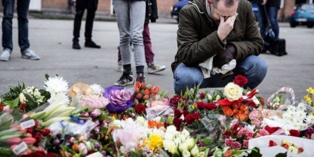 A man reacts next to flowers for the shooting victims outside the 'Kruttoende' cultural centre in Copenhagen,...