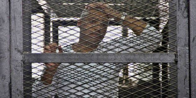Canadian-Egyptian acting Al-Jazeera bureau chief Mohammed Fahmy appears in a defendant's cage in a courthouse...