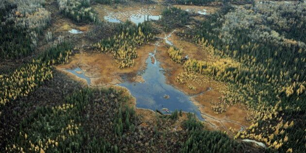 Aerial view of a lake and forests in the vicinity of oil sands extraction facilities near the town of...