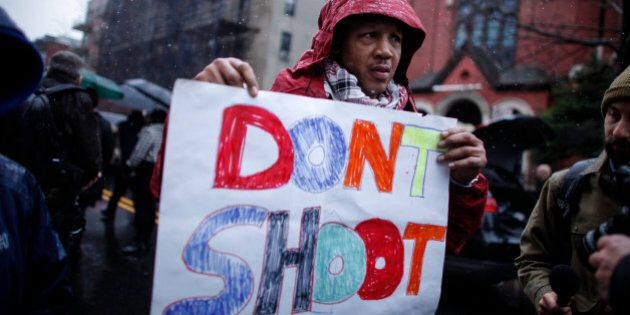 NEW YORK, NY - DECEMBER 6: A Man holds a banner as he demand justice during the funeral service of Akai...